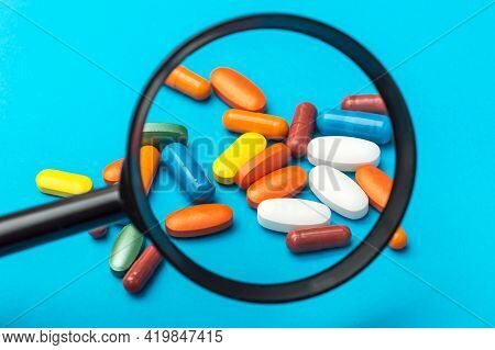Magnifying Glass With Pills On Blue Background.