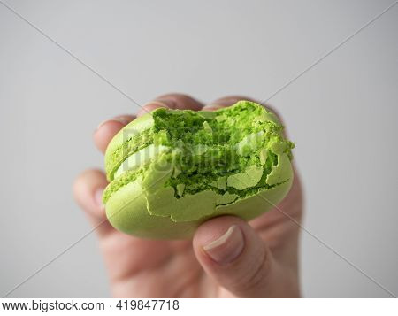 Close-up Of A Nibbled Green Macaroon Cookie In Your Hand On A White Background