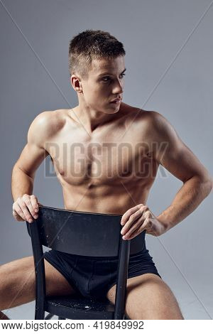 Handsome Man Athletic Physique Sitting On Chair Inflated Body Isolated Background