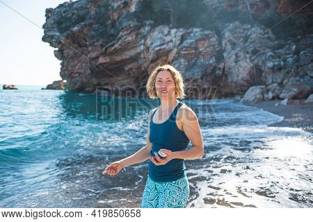 A Woman Walks Along The Sea Coast And Throws Stones Into The Water, The Girl Is Resting On The Beach