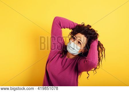 Fearful Expression Of A Woman Who Is Scared To Catch The Coronavirus. Yellow Background.