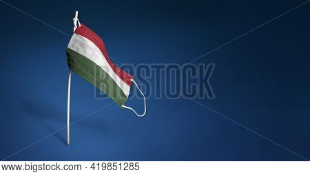 Hungary Mask On Dark Blue Background. Waving Flag Of Hungary Painted On Medical Mask On Pole. Concep