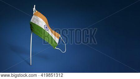 India Mask On Dark Blue Background. Waving Flag Of India Painted On Medical Mask On Pole. Concept Of