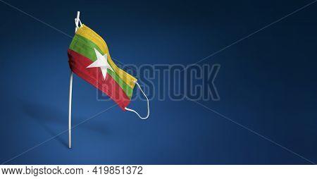 Myanmar Mask On Dark Blue Background. Waving Flag Of Myanmar Painted On Medical Mask On Pole. Concep