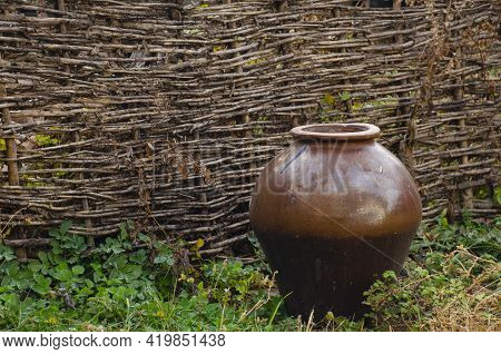 Pot At Wicker Fence At Countryside. Antique Traditional Tableware. Rural Landscapes. Old Handmade Cl