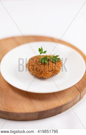 Pork Cutlet Garnished With Parsley On A White Plate