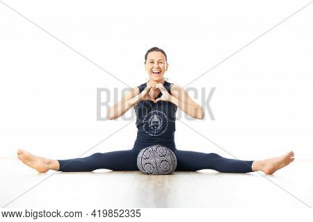 Restorative Yoga With A Bolster. Young Sporty Female Yoga Instructor In Bright White Yoga Studio, Ly