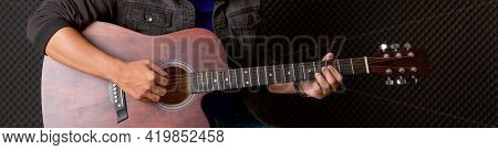 Closeup Musician's Hand Playing  An Acoustic Guitar In Front Of Black Soundproofing Walls. Musician