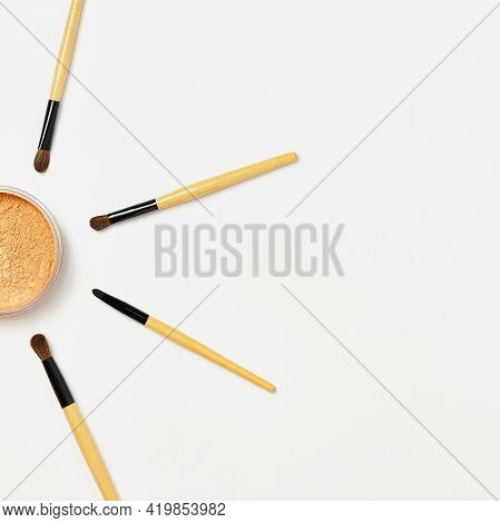 Brown Powder For Makeup And Four Brushes On A White Background.