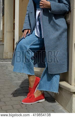 Woman In A Red Stylish Suede Loafer Shoes, Blue Jeanse, White Shirt And Trendy Checkered Coat Posing