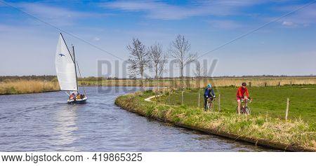 Friesland, Netherlands - April 27, 2021: Sailing Boat And Cyclists In The Landscape Of Friesland, Ne