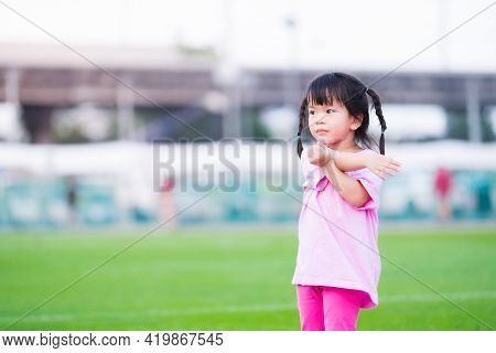 Cute Asian Girl Is Exercising In The Grass. Happy Child Is Using Both Arms And Twists The Body On Th