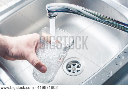 Hand Holding A Drinking Glass Over Kitchen Sink Filling It With Water Streaming From Faucet