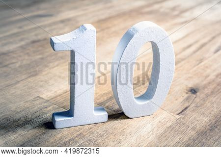 Number 10 Standing On A Brown Wooden Table