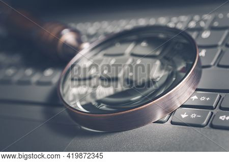 Vintage Loupe On A Gray Computer Keyboard - Search Engine Optimization Concept