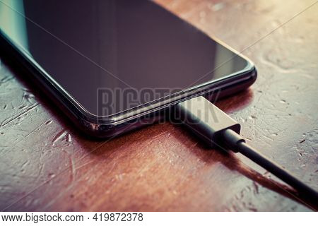 Black Smartphone With Connected Black Usb Cable On A Brown Wooden Table