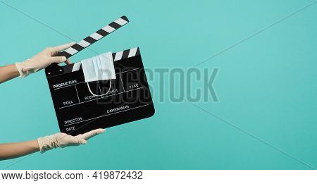Black Clapper Board Or Movie Slate With Face Mask In Hand That Wear Medical Gloves On  Mint Green Or