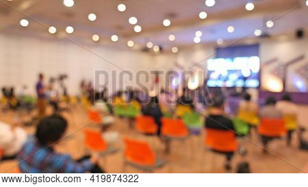Blurred Image Of People Sit In Hall For Seminar. Arrange Social Distancing Seat For Reduce Infection