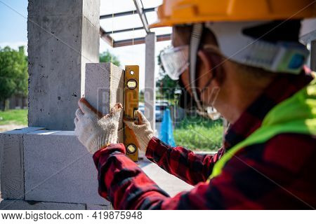 Close-up Bricklayer Builder  Using The Water Level, Check The Inclination Of Autoclaved Aerated Conc