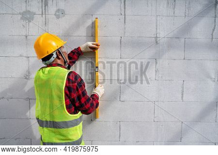 Bricklayer Builder  Using The Water Level, Check The Inclination Of Autoclaved Aerated Concrete Bloc