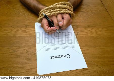 Contract And Tied Hands Holding Pen Ready To Sign. Bound Hands While Signing Unfair Contract. Contra