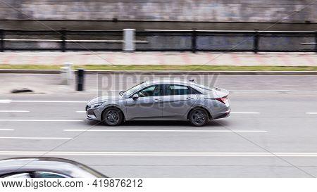 Hyundai Elantra Seventh Generation Cn7 At The City Road In Motion. Gray Car Driving Along The Presne