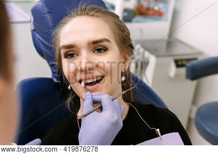 The Dentist Selects The Color Of The Enamel Of The Teeth To Whiten A Beautiful Girl Patient. Choose