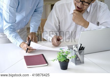 Diverse Male Mentor And Intern Talking Pointing On Paper