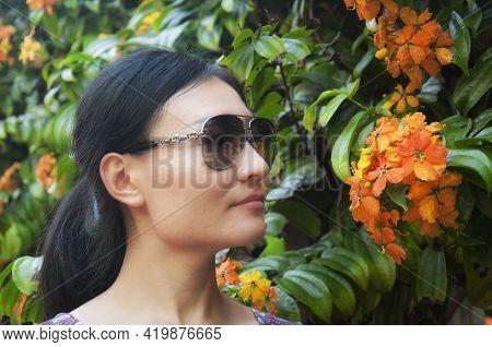 A Chinese Woman Wearing Sunglasselooking At Kock's Bauhinia, Phanera Kockiana, Tropical Vine Growing