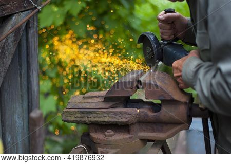 A Man Cuts A Pipe With A Grinder Sparks Fly Close-up. Cutting A Metal Pipe With A Splash Of Spark. E