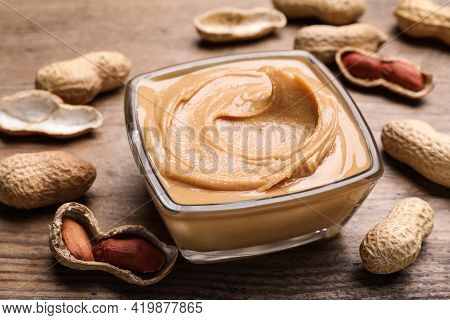 Yummy Peanut Butter In Glass Bowl On Wooden Table, Closeup