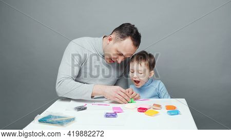 Photo Of Dad And Son Sculpting In Plasticine On Gray Background