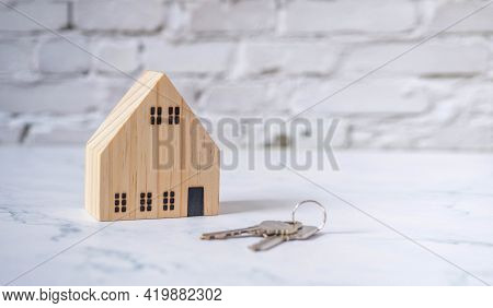 Miniature Wooden House With A Key On A White Brick Floor. Insurance, Mortgage, Trading, Home Brokera