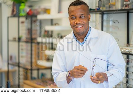 African Male Optician Standing With Arms Crossed In Optical Store. Eye Doctor, Optometris At Work.