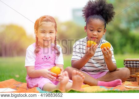 Two Little Happy Children Sitting On The Plaid, Eating Oranges Fruits And Looking At Each Other In T