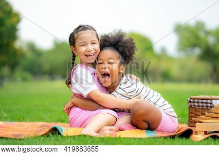 Two Happy Girls As Friends Hug Each Other In Cheerful Way. Little Girlfriends In Park. Childhood, Fa