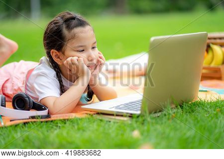 Little Girl Laying Down With Tablet Sitting In The Park. School Child Resting Outdoors.