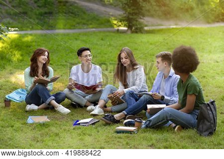 Group Of College Students Studying Outside Together, Preparing For Exams At Campus