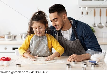 Happy Arab Father And Little Daughter Baking Together In Kitchen, Preparing Pastry