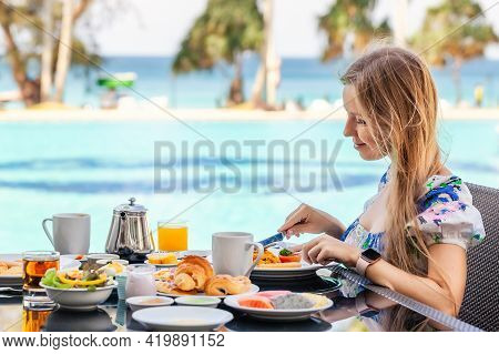 Woman On American Breakfast With Teapot On Table Next To Poolside In Resort. Morning Food Near Swimm