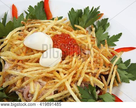 Russian Traditional Salad In The Form Of A Nest With Quail Eggs And Crispy Potatoes On White Plate