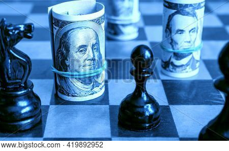 Dollar Bills And Chess, Us Cash On Chessboard In Blue Light. Finance Symbols And Game. Concept Of Mo