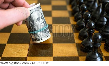Chess Game And Rolled Dollar Bills As White Move, Us Money On Chessboard. American Banknotes And Che