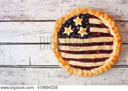 Patriotic American Flag Pie With Cherries And Blueberries. Above View On A Rustic White Wood Backgro