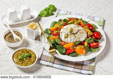 Spinach, Tomato And Burrata Cheese Salad With Basil Pesto Dressing On A Plate, Italian Cuisine