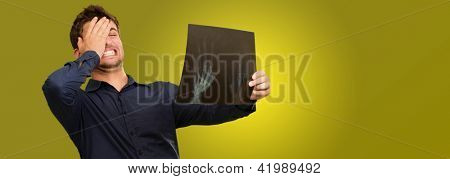Young Man Holding X Ray Report Gesturing  On Coloured Background