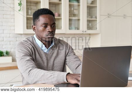 Adult Serious Professional African American Black Business Man Sitting At Kitchen Table Working Usin