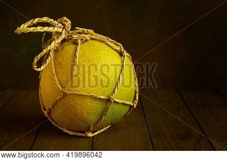 One Ripe Yellow Pomelo In A Rope Package On A Dark Background