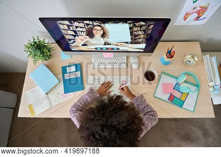 Table Top View Of Black African American Teen Pupil Writing Learning With Teacher Tutor Video Class
