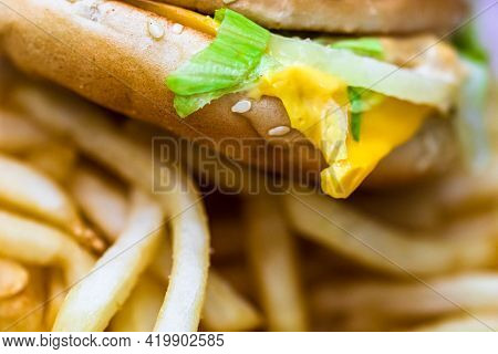 Close Up Detail Of Cheeseburger And French Fries. Food, Junk Food And Fast Food Concept